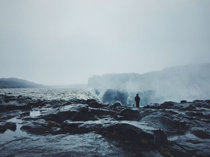 Rear view of person standing on cliff against sky during foggy weather