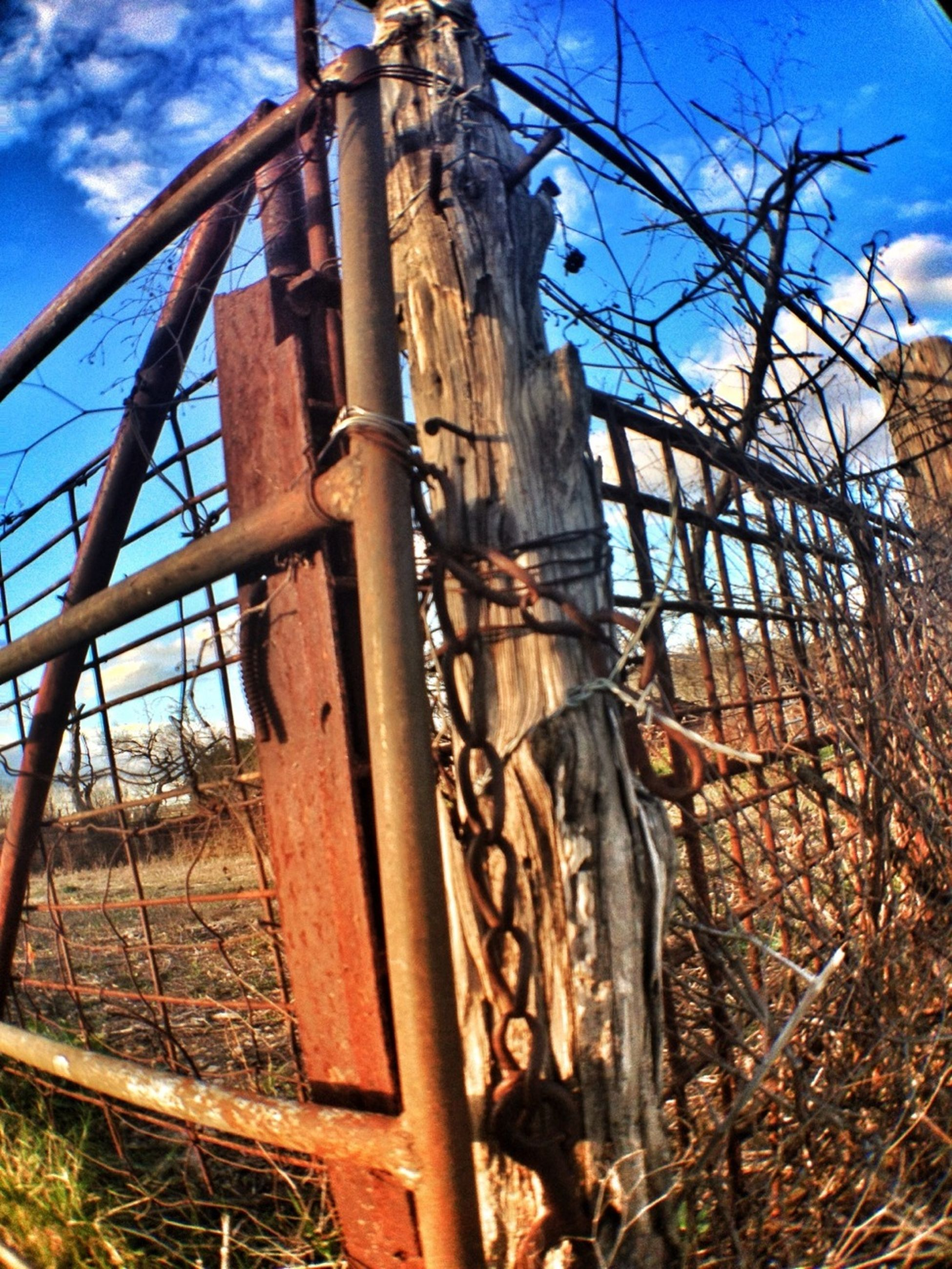 built structure, architecture, low angle view, sky, abandoned, building exterior, damaged, bare tree, old, metal, run-down, obsolete, deterioration, weathered, blue, fence, tree, rusty, day, outdoors