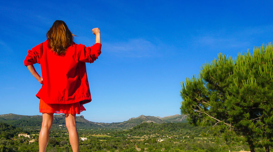 Rear View Of Woman Gesturing Fist While Standing Against Blue Sky