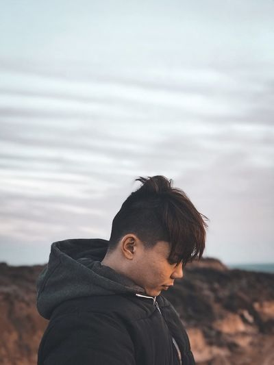 Young man standing against sky