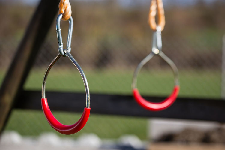 Close-up of handles hanging in jungle gym at playground