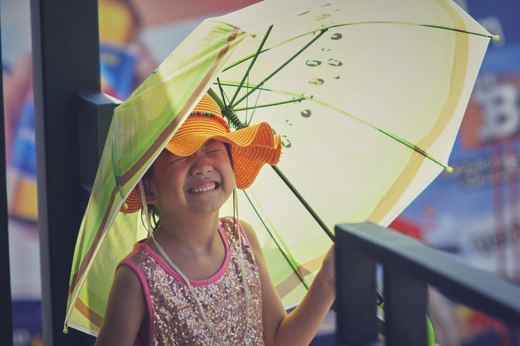 Cute smiling girl holding umbrella in city