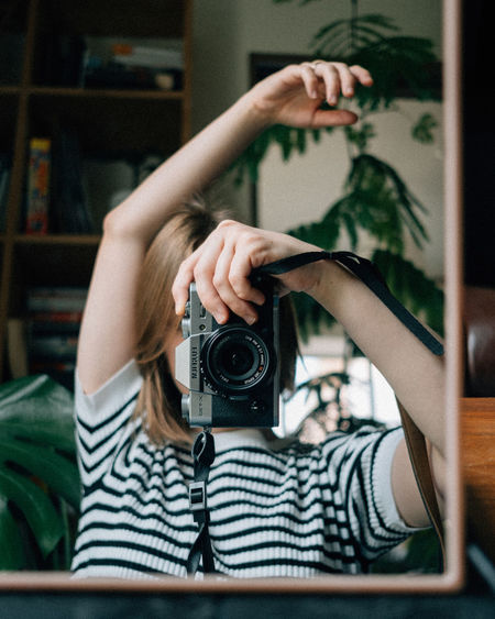 Man photographing camera at home