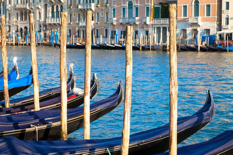 Close-up of gondolas on grand canal by wooden post against buildings