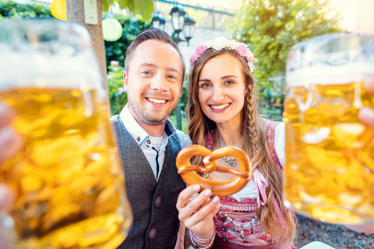 Portrait of smiling couple standing outdoors with beer glass