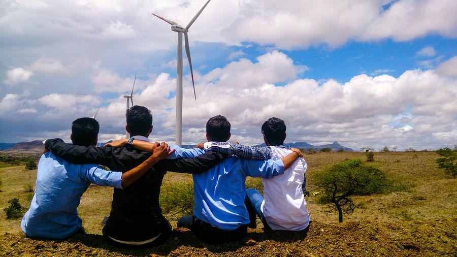 Rear view of friends sitting on field against windmills