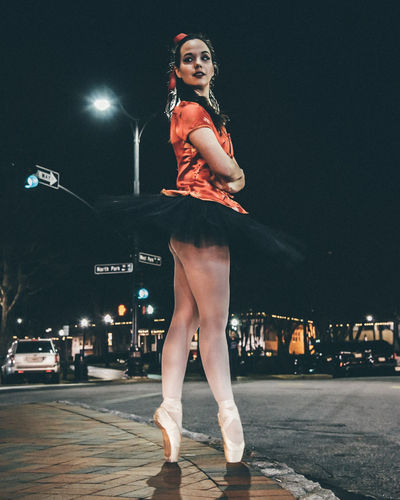 Full Length Of Ballet Dancer Dancing On Street At Night