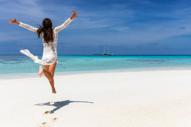 Happy traveler girl in white summer dress enjoys the tropical paradise beach with turquoise sea on the Maldives islands Sea Beach Water Land Human Arm Sky One Person Limb Leisure Activity Trip Arms Outstretched Holiday Vacations Beauty In Nature Full Length Real People Lifestyles Horizon Over Water Scenics - Nature Arms Raised Freedom Outdoors Positive Emotion Jumping Woman Traveler Holiday Dress Summer Happiness Travel Maldives Caribbean Tropical Paradise Freedom Turquoise Colored Ocean Island