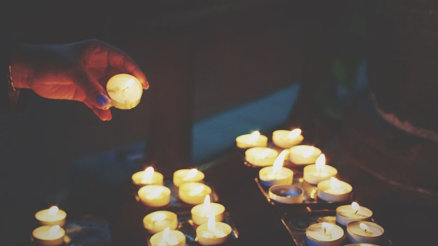 Cropped hand on woman holding lit candle at church