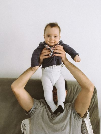 Portrait of smiling boy holding baby sitting against wall