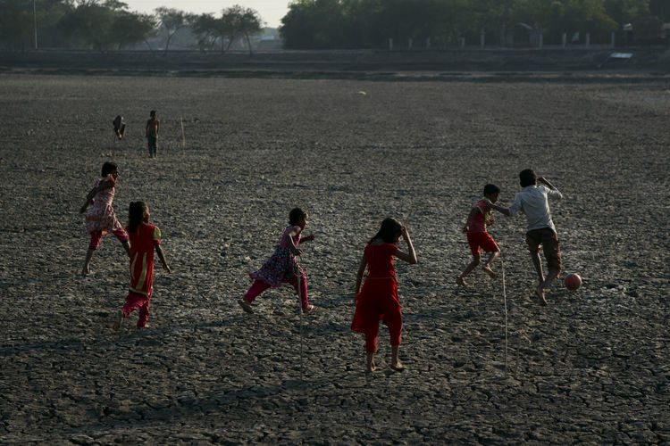 Group of people playing soccer on land