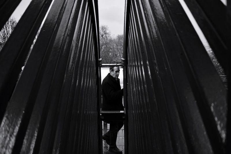 Side view of man seen through railing