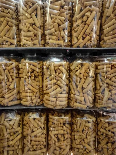 Full frame shot of spring rolls in glass jars on shelves at store