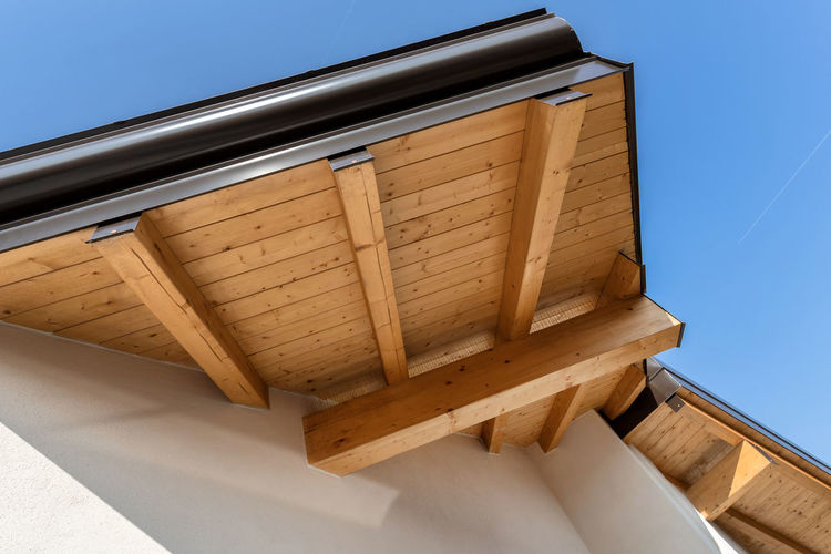New wooden warm ecological house roof with steel gutter rain system. Professional construction and drainage pipes installation. Eco materials. Gutter Roof House Rain New Construction Gutters Wooden Home Wood Architecture Detail Wall Sky Metal Exterior Downspout Guttering Blue Building Façade Closeup Steel Drain Pipe Protection Structure Outdoors Corner Drainpipe Design Drainage Overhang EAve Rooftop Eco