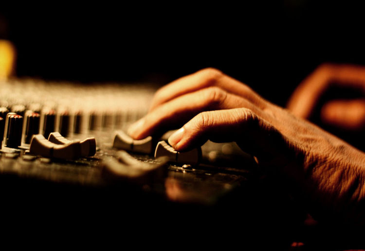 Cropped hands of person playing synthesizer