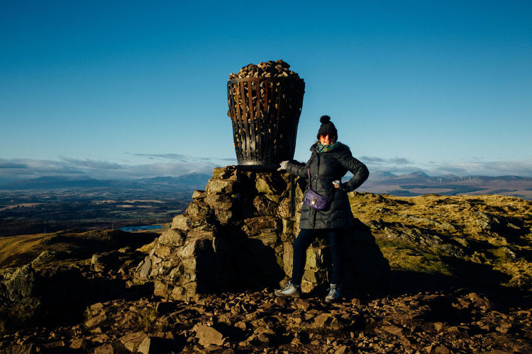 Full length portrait of woman standing by monument against blue sky at dumyat