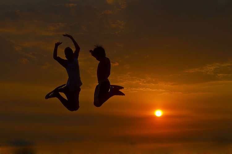 Low Angle View Of Silhouette Boys Jumping Mid-Air Against Sunset Sky