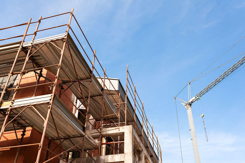 Low angle view of construction site against blue sky