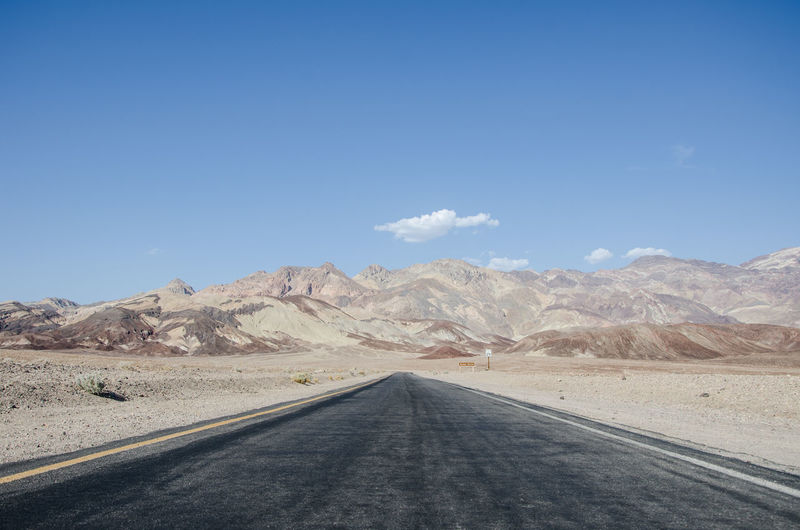 Road Amidst Desert Against Clear Blue Sky