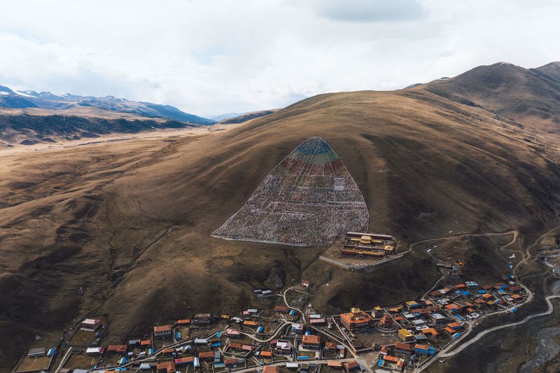 Aerial view of buildings by mountains against cloudy sky