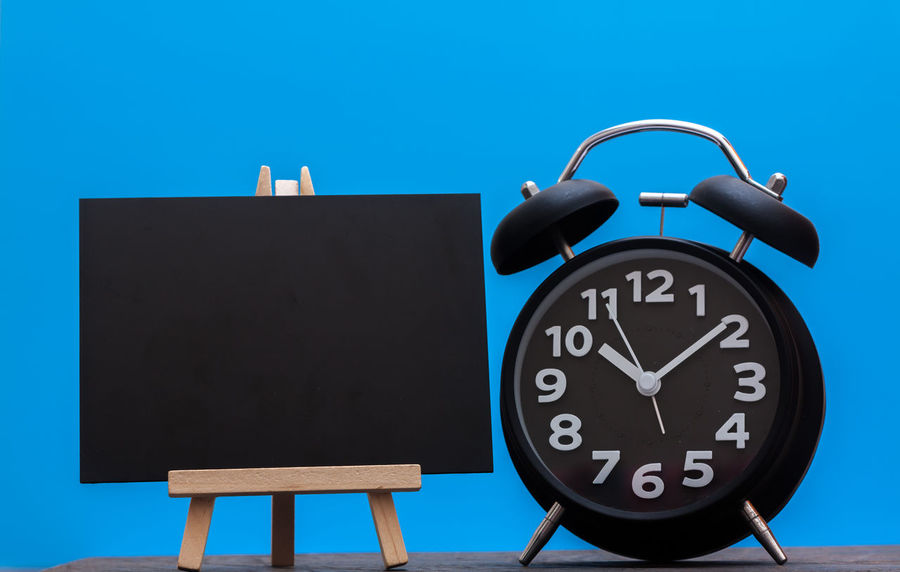 Blank blackboard and black clock with blue back ground Alarm Clock Clock Clock Face Close-up Concept Day Hour Hand Indoors  Minute Hand No People Time