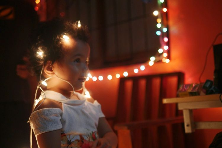 Side view of cute girl with illuminated string lights at night