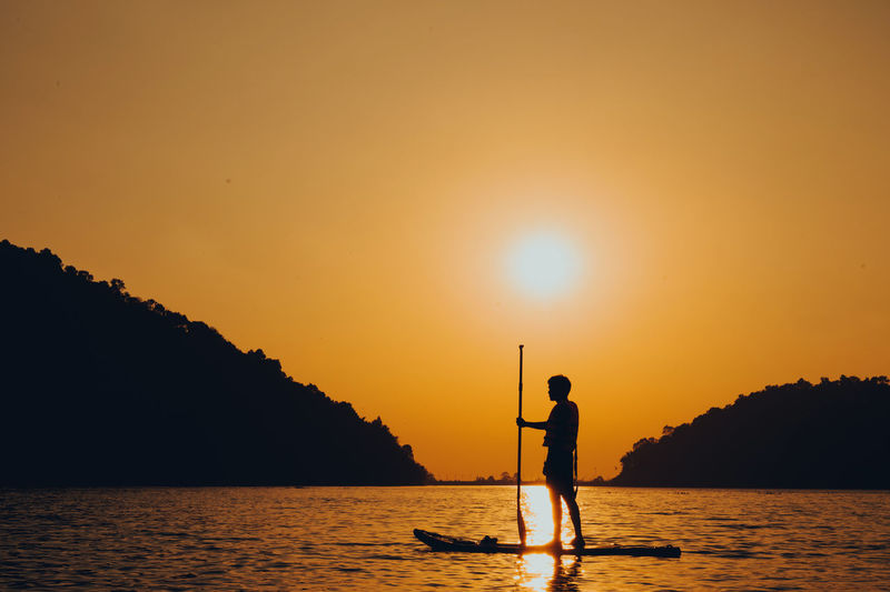 Silhouette man standing in sea against orange sky