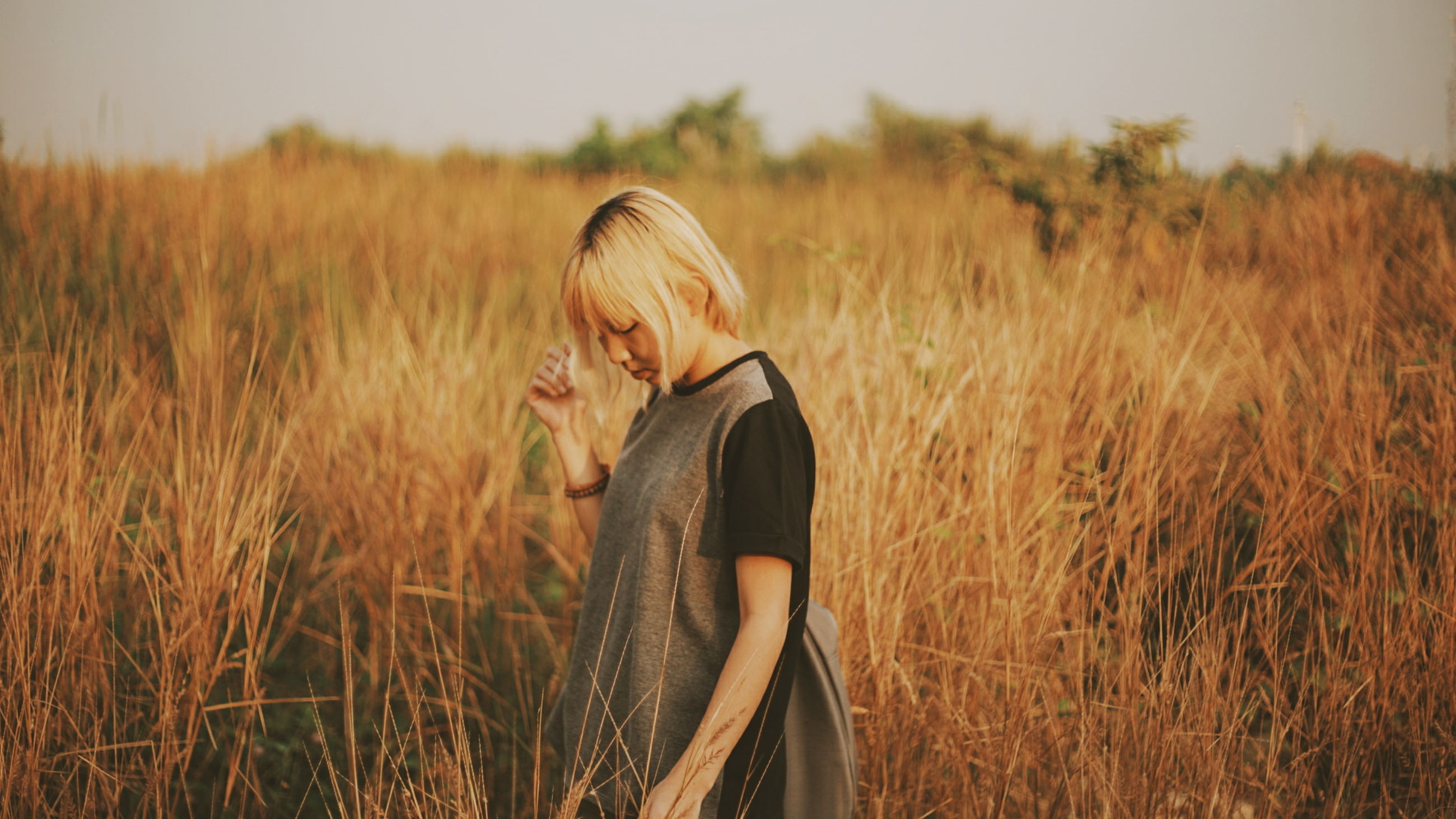 lifestyles, field, grass, leisure activity, young adult, standing, young women, casual clothing, three quarter length, plant, person, nature, tranquility, waist up, landscape, long hair, sky, outdoors