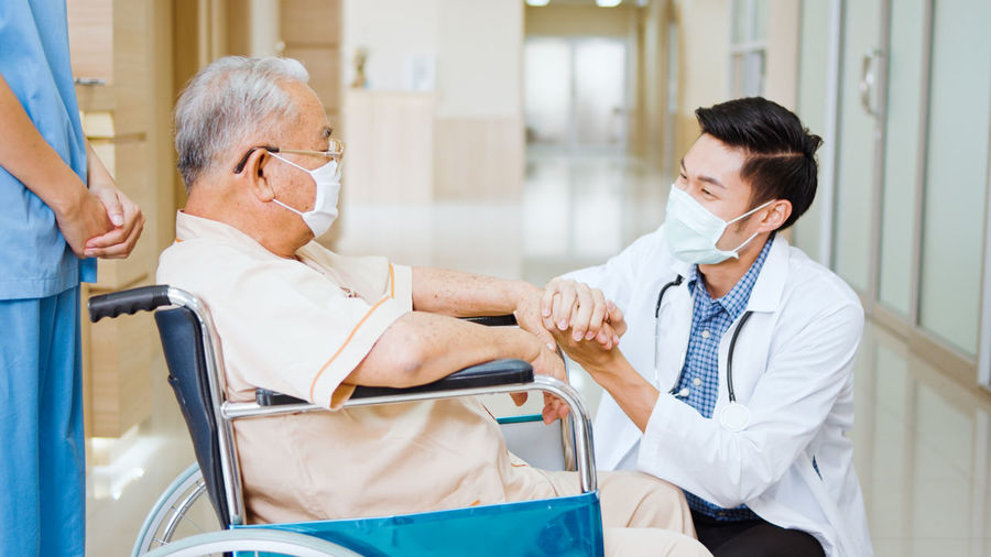Smiling doctor wearing flu mask consoling patient in hospital