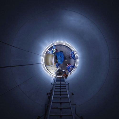 Low Angle View Of Workers In Illuminated Wind Turbine At Night