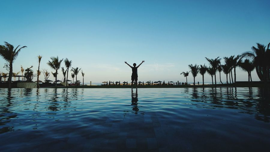 Silhouette boy with arms raised standing by swimming pool against clear sky