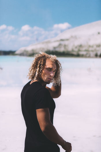 Curly blond man dressed in all black. posing on the sea beach. Impressive shoot, trendy hairstyle. Summer time. Adult Beautiful Woman Curly Hair Focus On Foreground Hair Hairstyle Land Leisure Activity Lifestyles Looking At Camera Nature One Person Outdoors Portrait Real People Standing Waist Up Water Young Adult