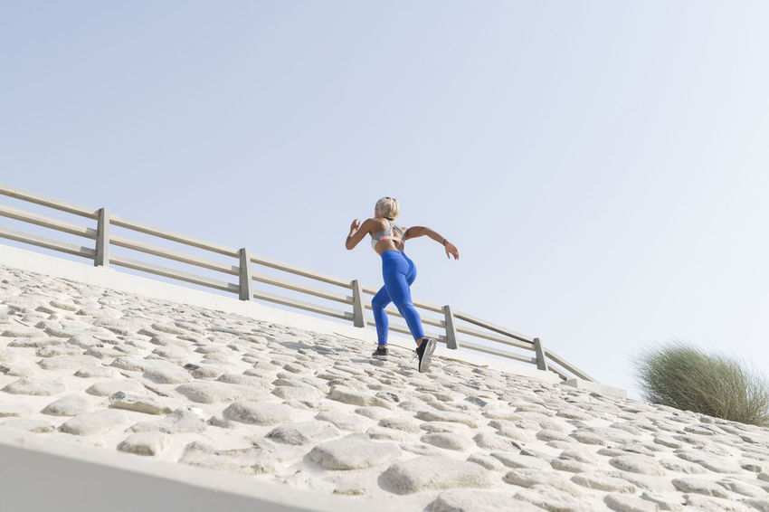 Middle Eastern Girl with short braided hair running uphill hill on a urban side street wearing blue and gray fitness outfit on a hot bright sunny day. Exercising Jumping Off Rocks Sitting Adult Bright Day Clear Sky Copy Space Day Dusty Effort Fitness Model Front View Full Length Hot Day ☀ Human Arm Land Leisure Activity Lifestyles Low Angle View Middle Eastern Woman Nature One Person Outdoors Real People Sky Sport Sports Clothing Standing Stretching Vitality Young Adult