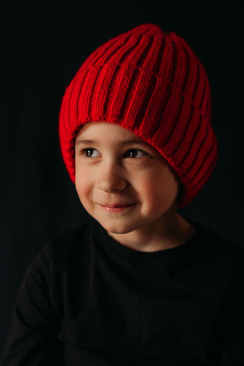 Portrait of boy wearing hat against black background