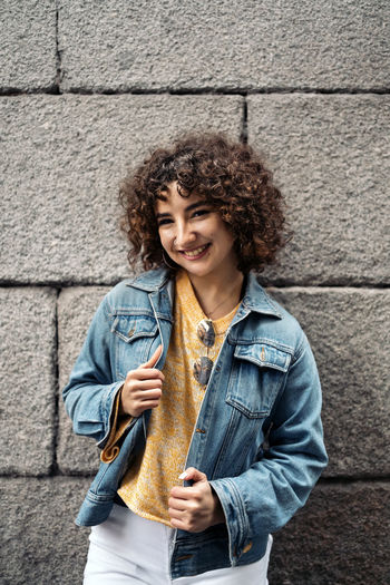 Young woman smiling while standing against wall
