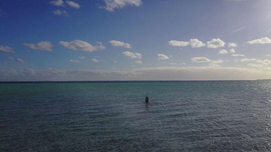 Man in sea against sky at beach