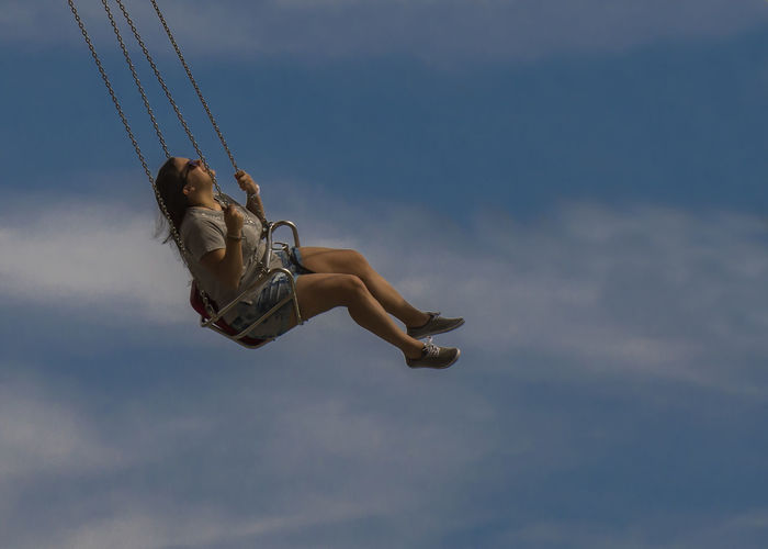 Full length of young woman swinging on chain swing ride against sky