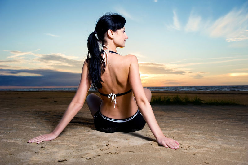 Young brunette sitting on the beach near the sea Cloud Sitting Slim Woman Beach Beautiful Woman Brunette Caucasian Cloud - Sky Lifestyles Nature One Person Outdoors People Real People Scenics Sky Sport Sportive Sportwear Sundown Sunset Women Young Adult Young Women