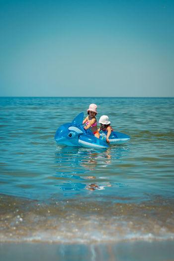 Siblings on inflatable rafts in sea against blue sky
