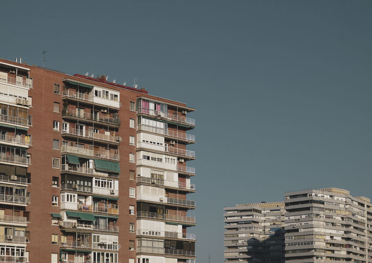 Low angle view of residential buildings in madrid, spain, against blue sky