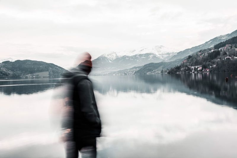 Blurred motion of teenage boys standing at lake against sky