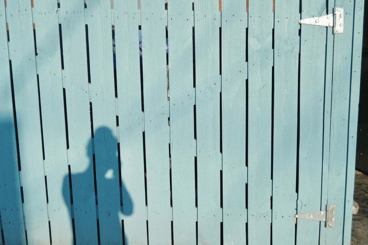 Shadow Of Person On Wooden Fence
