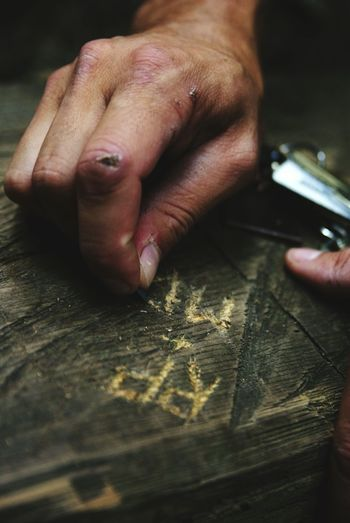 Close-Up Of Man Hand Engraving On Wood