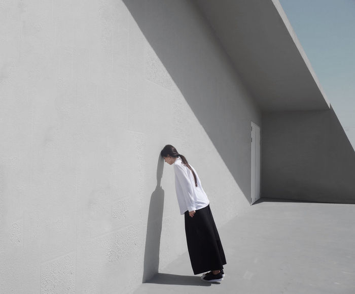 Full length side view of woman leaning on white wall
