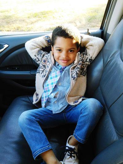 Portrait of smiling boy sitting in car