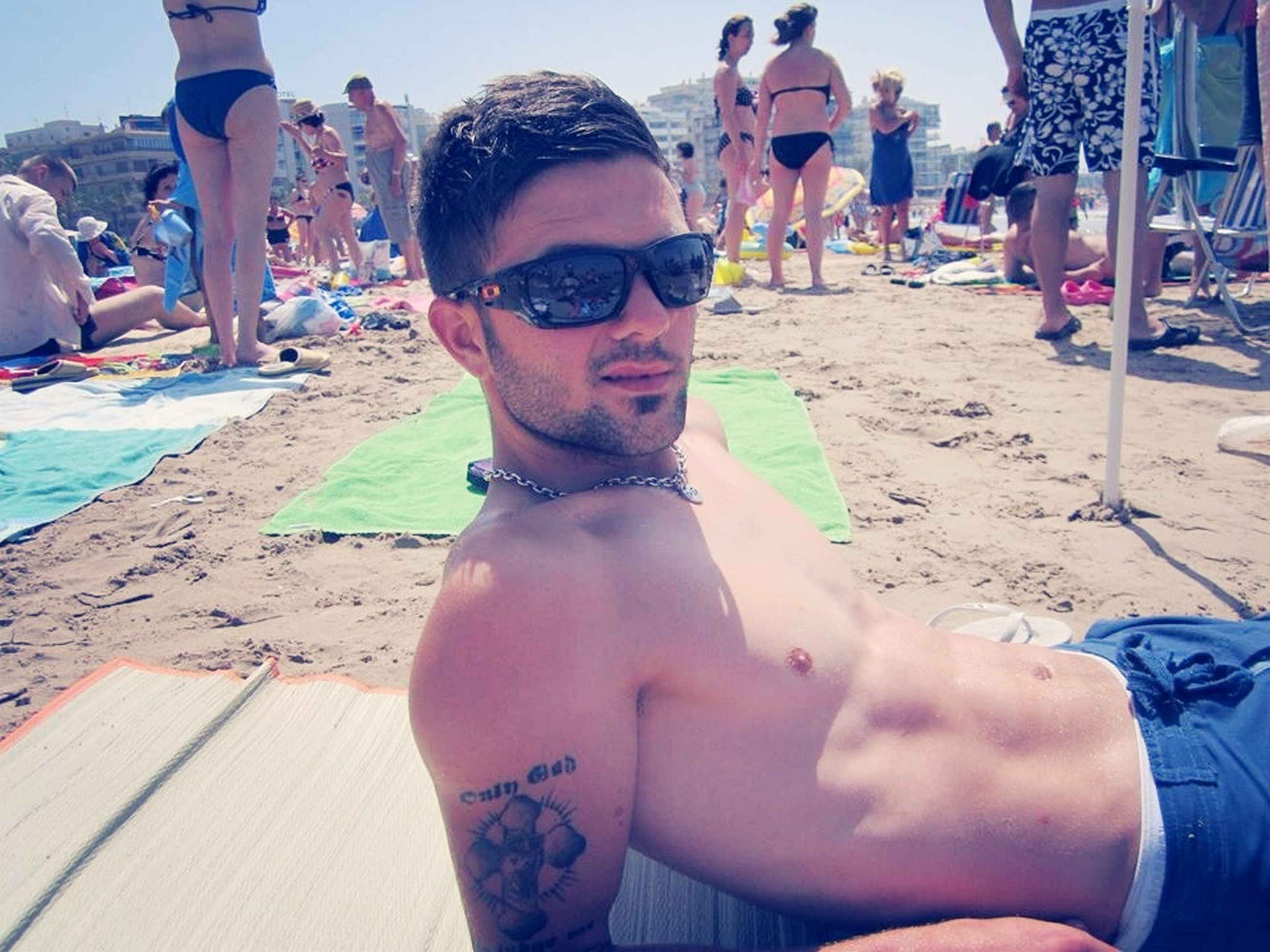 lifestyles, beach, leisure activity, sand, sunglasses, sunlight, person, young men, young adult, casual clothing, vacations, incidental people, portrait, shore, front view, outdoors, day, sitting