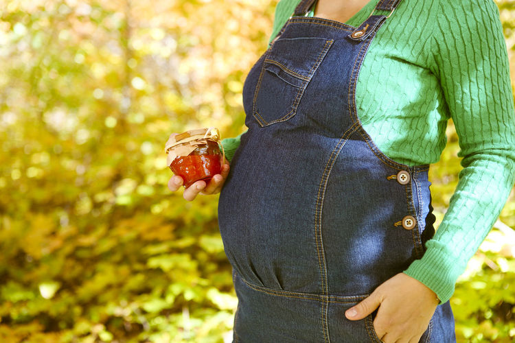Midsection of woman holding fruit on tree