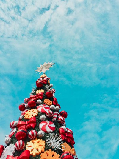 Low angle view of christmas decorations against blue sky