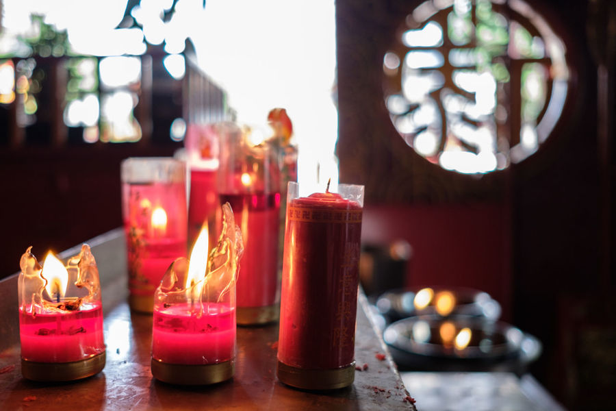 red candles burning Altar Burning Candle Close-up Day Diya - Oil Lamp Flame Focus On Foreground Glowing Heat - Temperature Illuminated Indoors  No People Oil Lamp Place Of Worship Red Religion Spirituality Table Tea Light