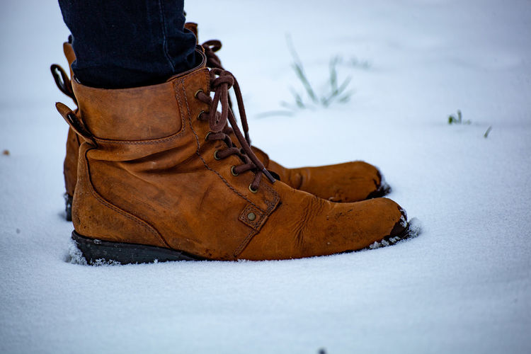 Low Section Of Person Wearing Leather Shoes While Standing On Snow